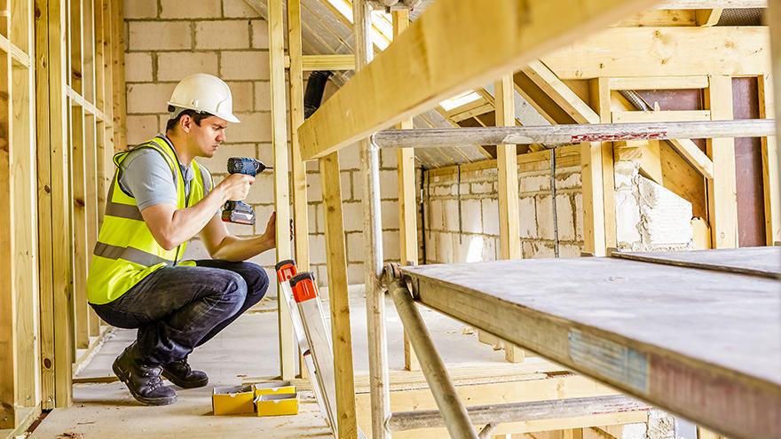 homem construindo um prédio.