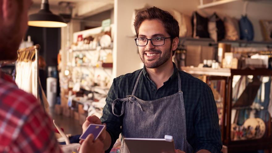 Vendedor entregando cartão para o cliente.