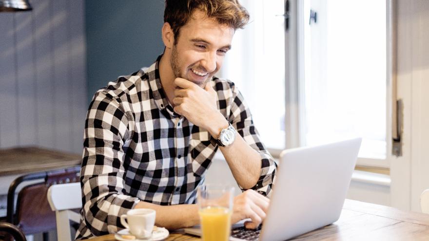 Capa da matéria do Blog da CISS. Homem jovem sentado em frente ao computador com um copo de suco ao lado