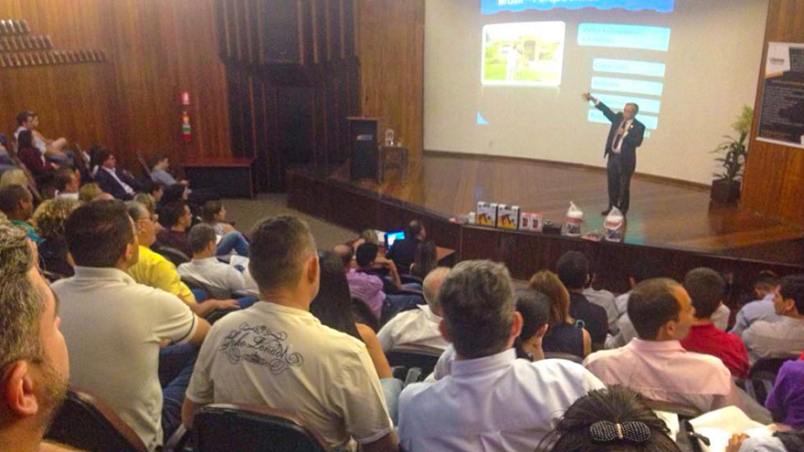 Pessoas num auditório assistindo uma palestra.
