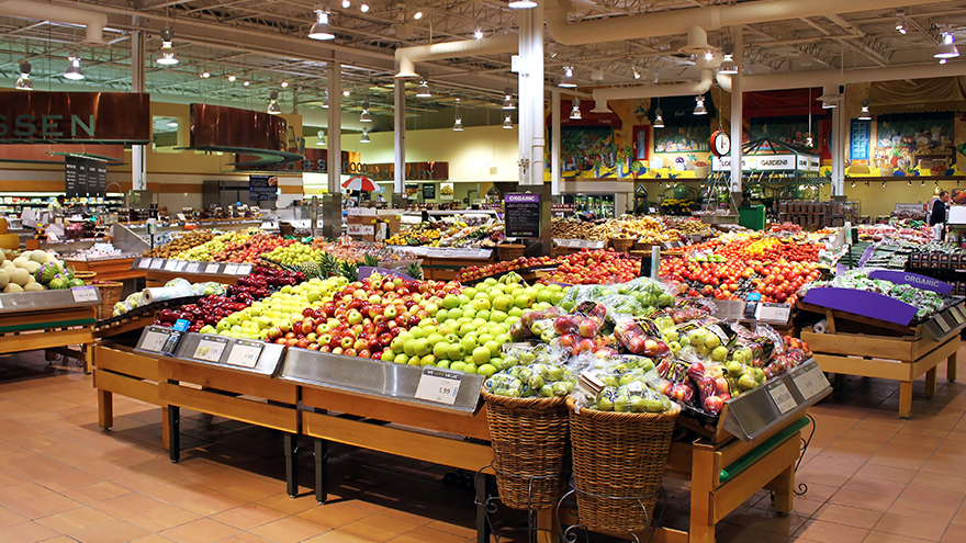 Hortifruti do supermercado com bancadas de frutas e verduras.