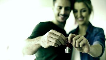 Casal segurando a chave da casa própria, olhando pra frente.